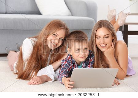 Lesbian couple with foster son in living-room. Adoption concept