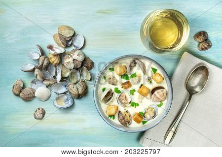 An overhead photo of a bowl of clam chowder, decorated with fresh parsley and croutons, on a teal texture with a spoon, a glass of white wine, mollusk shells, and a place for text