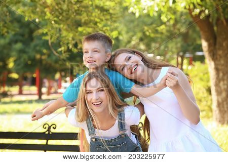 Lesbian mothers with foster son having fun in park