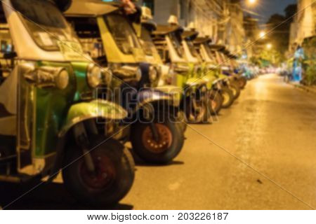 Blurry Background of Three-wheel taxi parked on the side of the road. In Thailand, Thailand nationals call these cars that
