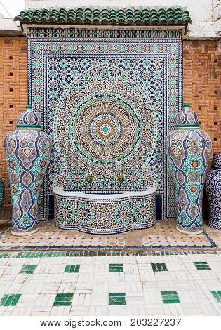 Fez Morocco - May 07 2017: Typical handmade moroccan mosaic fountain and vases in the courtyard of the Mosaic Factory in Fez Morocco Africa.