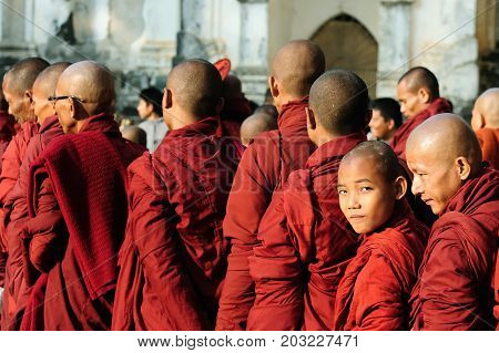 BAGAN MYANMAR - 19 JANUARY 2011: Young Buddhist monks standing in a queue for gifts
