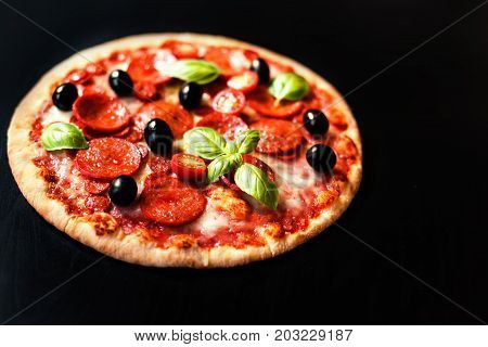 Pizza pepperoni with Ham Pepperoni and Bacon on dark background with fresh ingredients for you to design and restaurant menu. Delicious Homemade Meat pizza
