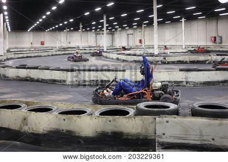 MOSCOW - JAN 2, 2017: Man in helmet drives in go-kart with raised arm on track during competition, other drivers out of focus