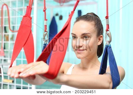 Post-traumatic rehabilitation of shoulder joints. Woman doing exercises on hangers.
