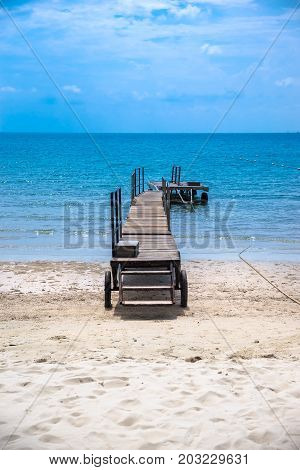 Tropical lonely beach deck under blue sky