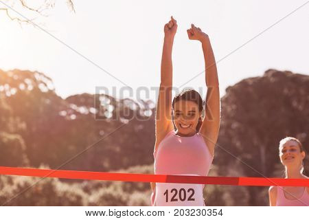 Happy female athlete with arms raised crossing finish line on sunny dy