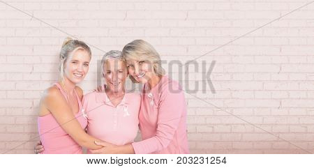 Portrait of smiling daughters with mother supporting breast cancer awareness against white wall