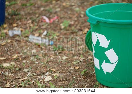 A close-up picture of a bright green recycling bin in the park. A plastic container for rubbish recycling next to a plastic bottle on a blurred ground background. Ecology, nature protection concept.