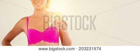 Mid section of smiling woman in pink bra holding breast cancer awareness ribbon