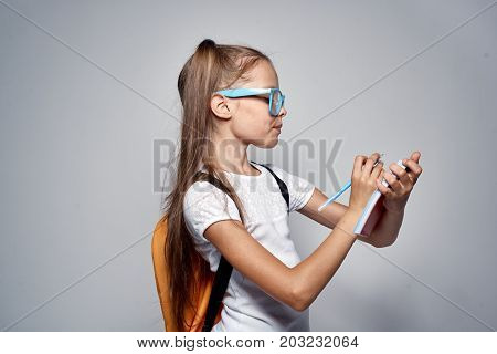 little girl with glasses writes in a notebook, portrait, schoolgirl.