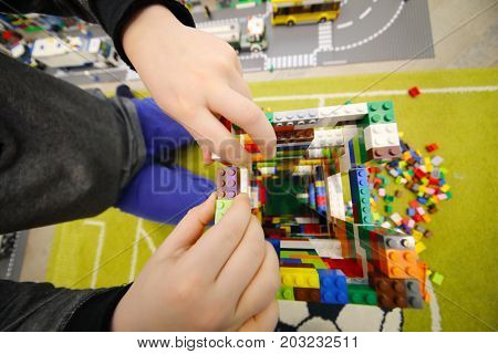 MOSCOW - DEC 5, 2016: Hands of boy playing with erector set Lego, The company Lego Group was founded in 1932