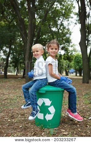 Young girl and boy relaxing after cleaning park on the green recycle bin, which are on earthen background. Enviromental protection concept. Uncleaned outside territory. Helping children in the park.