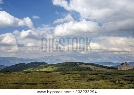 plain. Rock. in the background of the mountain there is a blue sky and clouds.