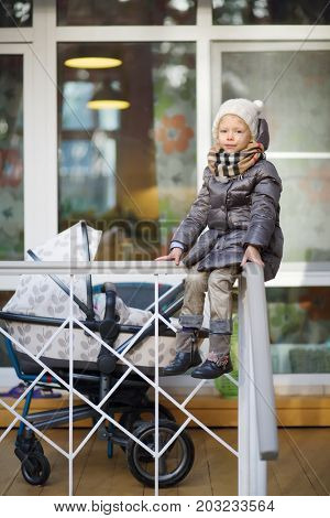 MOSCOW - OCT 25, 2016: Girl (with MR) sits on railing at terrace near house at summer residence of Mosdachtrest company, which manages summer houses fund, services and rents out-of-town property