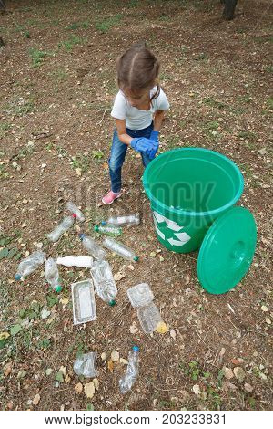 Vertical photo of small girl with bright recycle bin on earthen background with different rubbish and dry yellow leaves. Uncultivated outside terrain. Helping child. Concept of envirometal protection.