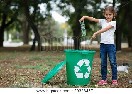 A full-length portrait of a cute little girl putting a plastic bottle in the recycling container. Child picking up the plastic trash on a blurred natural background. Ecology, nature pollution concept.
