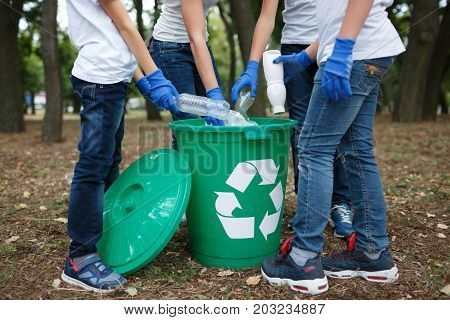 A side view of child's legs and hands in blue latex gloves. A group of schoolers throwing out the plastic trash in a green recycling bin. Environment, ecology, nature pollution concept.
