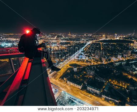 MOSCOS - OCT 17, 2015: Man sits with camera on skyscraper near beacon at night