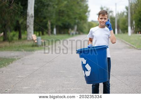 A portrait of a handsome little teenager holding a dark blue recycling container. Boy collecting the urban trash and speaking on a phone on a blurred natural background. Ecology, pollution concept.