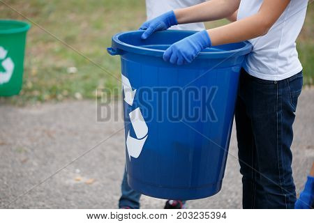 A close-up picture of child's hands holding a dark blue recycling container. Child collecting the plastic trash on a blurred natural background. Ecology, nature pollution concept. Copy space.
