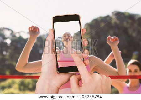 Hands touching smart phone against cheerful young athlete crossing finish line