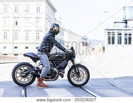 Motorcycle rider on custom made scrambler style cafe racer in the city