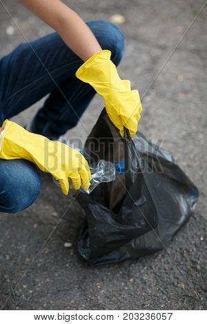 A close-up picture of child's legs and hands in yellow latex gloves. Children picking up the plastic trash. Environment, ecology, nature protection, pollution concept. Copy space.