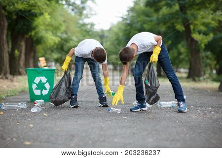 A full-length portrait of children in yellow latex gloves. A couple of children collecting the plastic trash. Environment, ecology, nature protection, pollution concept. Copy space.