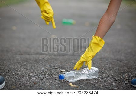 Side view of children's hands picking up the plastic bottle. A close-up picture of hands in yellow latex gloves. Environment, ecology, nature protection, pollution concept. Copy space.