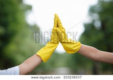 A close-up picture of children's hands in yellow latex gloves. Young ecologists giving each other five on a blurred natural background. Environment, ecology, nature protection, pollution concept.