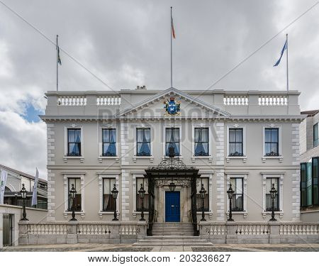 Dublin Ireland - August 7 2017: The light gray historic Mansion Room Banquet Hall in Dawson Street under heavy sky and with flags. Black lanterns and entrance awning.