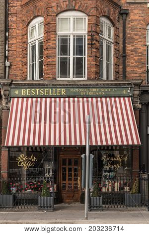 Dublin Ireland - August 7 2017: Red brick facade and large white-red awning of National Bible Society of Ireland book store and coffee bar in Dawson Street named Bestseller. Dark green trim around windows.