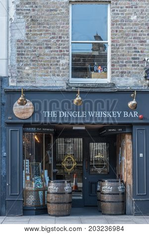 Dublin Ireland - August 7 2017: blue-gray facade of the Dingle Whiskey Bar and tasting room in Nassau Street. Wooden kegs in front of display windows.