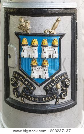Dublin Ireland - August 7 2017: Coat of Arms fresco colorfully edged on every historic lantern of the city. Shows three white castles on sky blue background with city slogan in Latin.