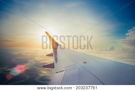 Wing of airplane flying above the clouds in the sunset sky background. View form the window plane through.