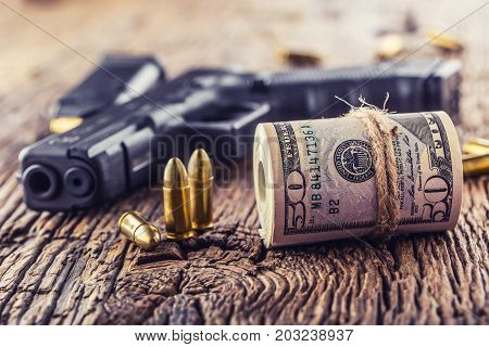 Gun and money. 9 mm pistol gun bullets strewn and roll dollar banknotes on rustic oak table.