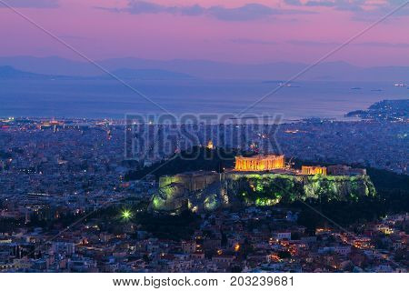cityscape of Athens with illuminated Acropolis hill and Pathenon temple at night, Greece