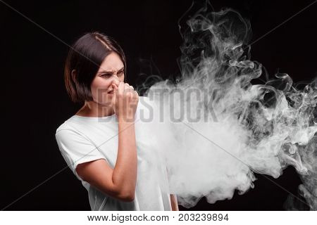 A close-up portrait of a brunette girl in a cloud of smoke. A young woman pinches her nose because of the cigarette smoke. A female in a white T-shirt doesn't like a tobacco smoke. Healthcare concept