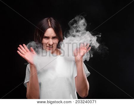 A portrait of a brunette girl in a cloud of smoke on a black background. A young woman wrinkles her face because of the cigarette smoke. A female in a white T-shirt hates a tobacco smoke. Copy space.