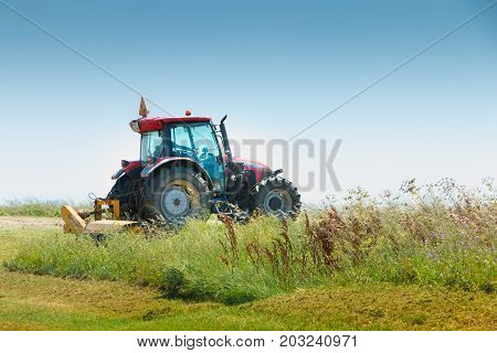 Aiguillon-sur-Mer France France - July 06 2016 : red tractor equipped with a large mower cuts the grass in a meadow