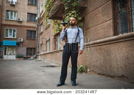 A full-length portrait of a handsome man with a beard holding a gun on an urban background. A dangerous elegant killer in classic clothes with a rifle. Danger, gangster concept. Copy space.
