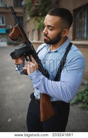 A close-up portrait of a handsome stylish man with a beard holding a gun on an urban background. A dangerous confident killer in classic clothes with a rifle. Danger, gangster, crime concept.