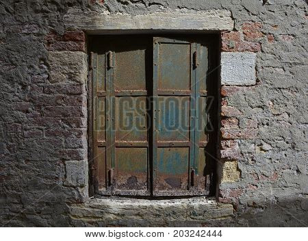 An old window with a metal shutter in a derelict building in the Dorsoduro quarter of Venice