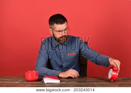 Man With Beard And Glasses Checks Time Holding Alarm Clock
