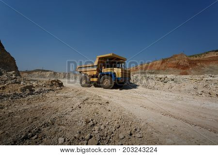A side view of a big yellow transporter on a natural sandy quarry background. A machinery equipment with a laden ground. Dump trucks. Technology, cargo, commerce, transport concept. Copy space.