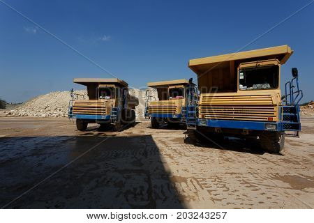 Dump trucks. A front view of three big yellow transporters on a natural sandy quarry background. A machinery equipment with a laden ground. Technology, cargo, commerce, transport concept. Copy space.