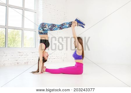 Two young girls are engaged in sports exercises in the gym. Fitness. The concept of sport dance and a healthy lifestyle.