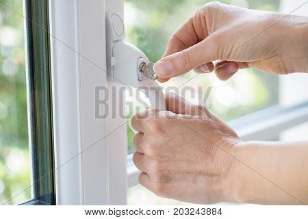 Close Up Of Woman Turning Key In Window Lock