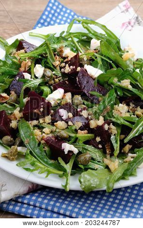 Beetroot salad with arugula with feta and capers sprinkled with crushed nuts